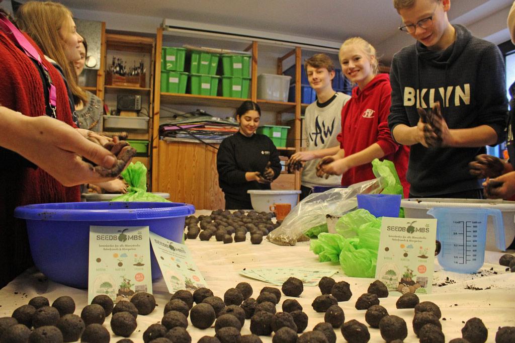 Junge Teilnehmer einer Jugendkonferenz rollen Erde, Dünger und Samen zu Samenkugeln