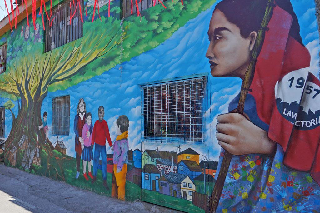 La Victoria – ein Ort zum Leben: Ein wandbild zeigt eine Frau mit Kopftuch, spielende Kinder, bunte Häuser und einen riesigen Baum - so ist die Siedlung La Victoria in 60 Jahren gewachsen und gediehen!