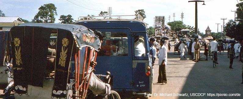 Straßenszene in Dhaka, der Hauptstadt von Bangladesch, mit Rikschas und vielen Fußgängern