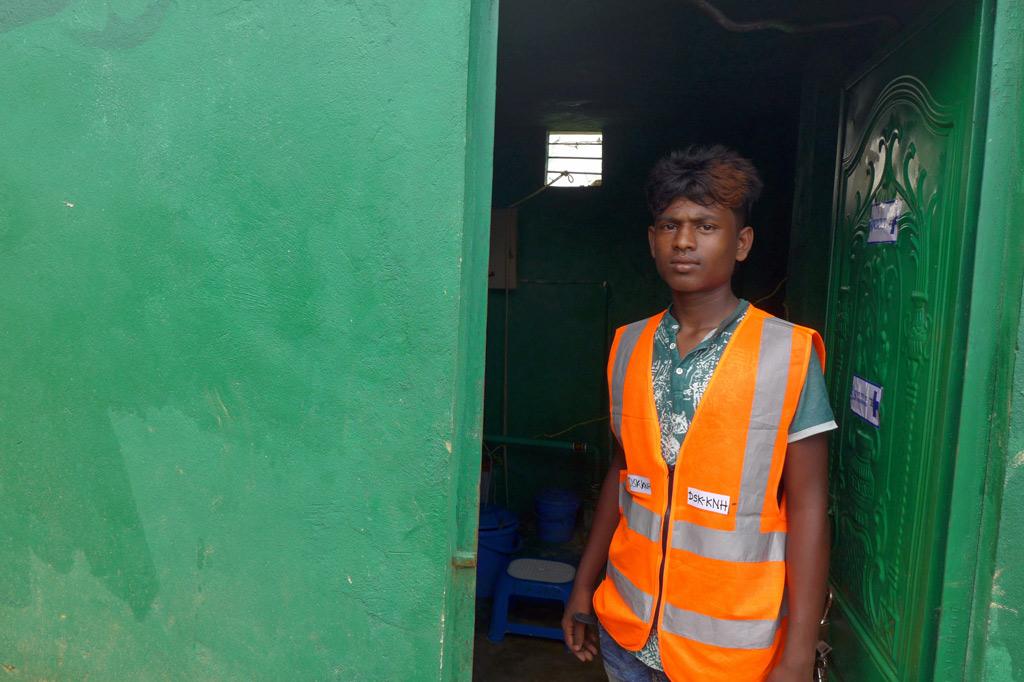 Der junge Rohingya Malek vor einem Pumpenhaus. Er Verantwortlich für die Wasserversorgung: Malek überwacht den ordnungsgemäßen Betrieb einer Wasserpumpe, die mit Kindernothilfe-Spenden finanziert wurde.