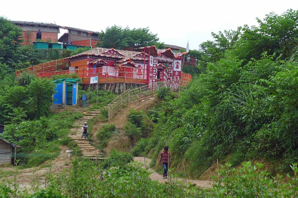 Eine Treppe im Rohingya-Lager führt zu einem bunt bemalten Haus auf Stelzen.