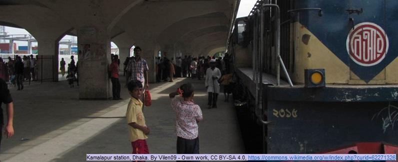 Ein Bahnsteig im Bahnhof Kamalapur, der zugleich Hauptbahnhof der bengalischen Hauptstadt Dhaka ist. Zu sehen sind eine Lokomotive und Passsagieren; im Vordergrund zwei Jungen