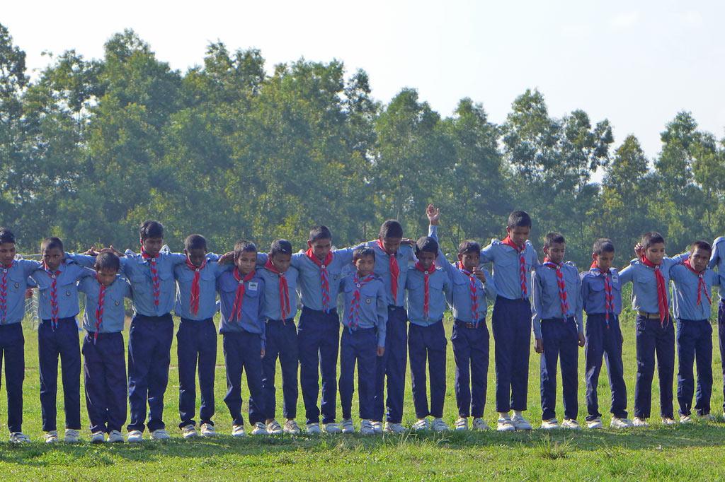 Schüler im Children´s City Panchagarh, gekleidt in hellblaue Hemden und dunkelblaue Hosen, bilden eine Kette