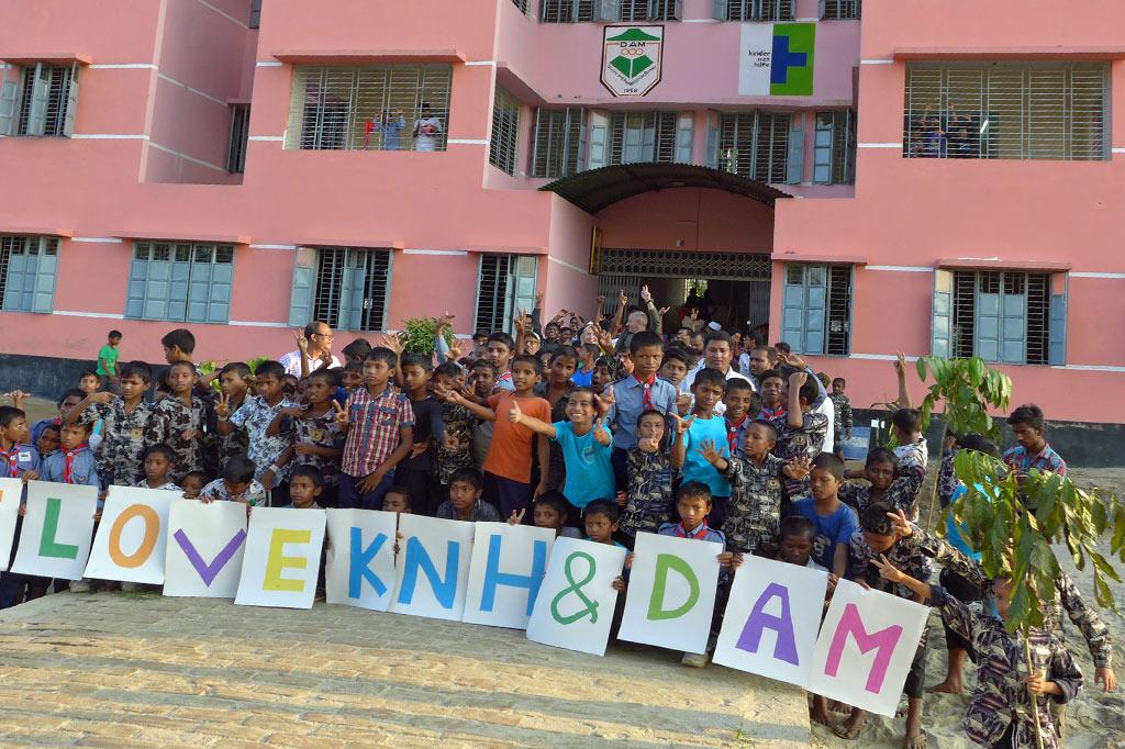 """Den Bahnhof und die Straße hinter sich gelassen - jubelnde Kinder vor dem neuen Schutzzentrum halten einen Willkommensgruß: """"We love KNH & DAM"""""""