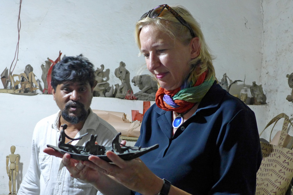 Die Autorin Katrin Weidemann hält die kleine Skulptur eines Ruderbootes mit Ruderern in der Hand. Im Hintergrund der Künstler Tejosh Halder Josh