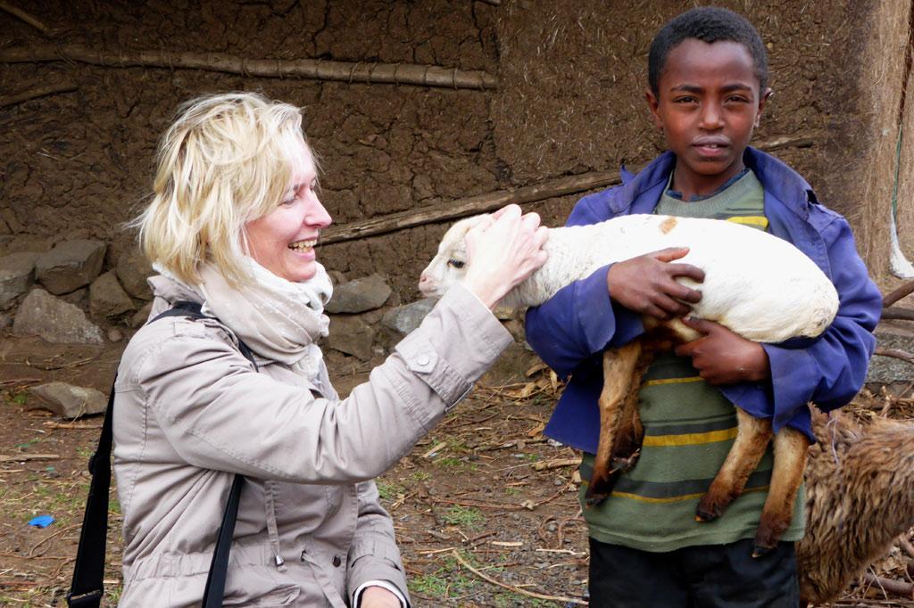Eine Frau und ein Kind mit einem Lämmchen auf dem Arm