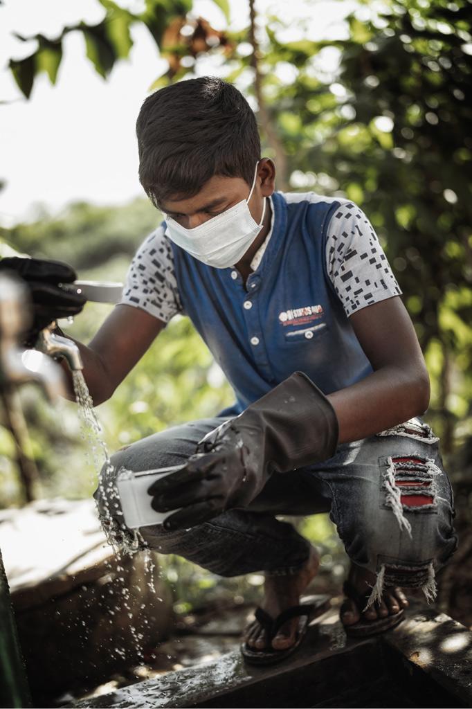 Ein Jugendlicher mit Munschutz hockt vor einem Wasserhahn und sammelt Wasser in einem Gefäß.