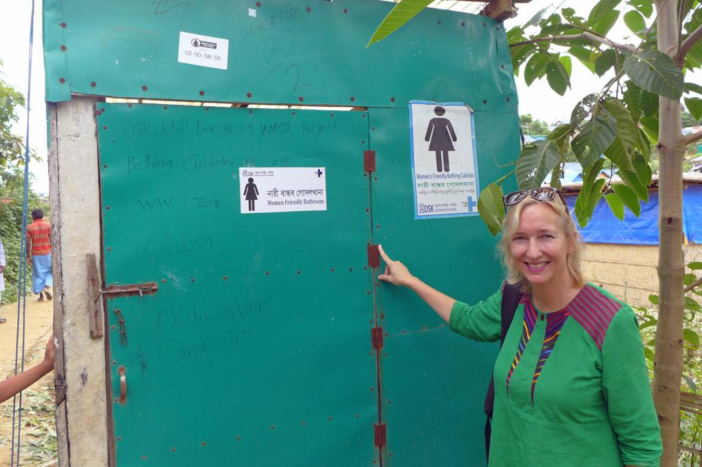 Katrin Weidemann vor einem der leuchtend grün gestrichenen Toilettenhäuschen