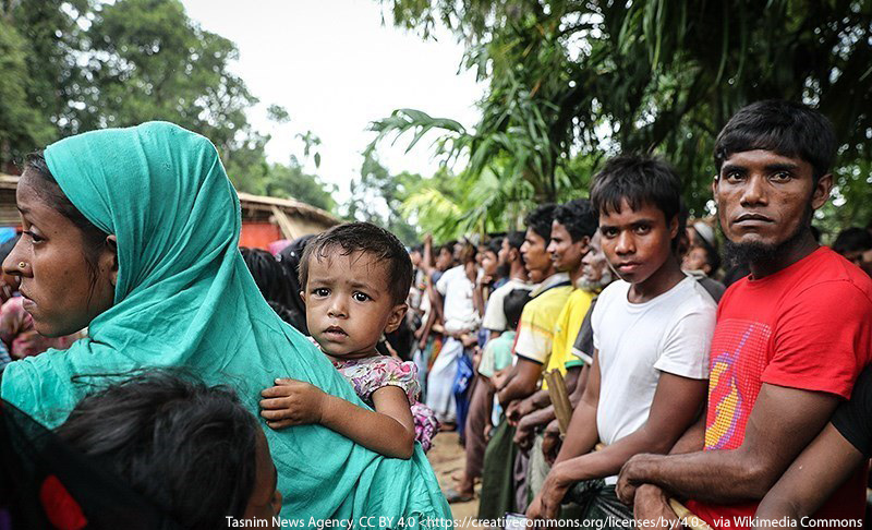 Eine Reihe von jungen Rohingya mit einer Frau mit Kinde auf dem Arm im Vordergrund